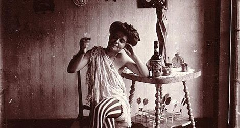 """Storyville. Seated woman wearing striped stockings, drinking """"Raleigh"""" Rye."""