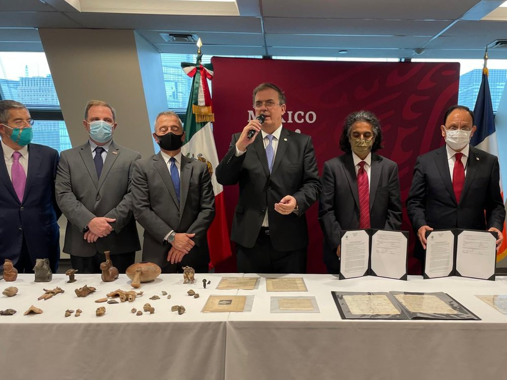 Seven people in suits and ties stand in front of a table with antiquities and 16th century documents laid out
