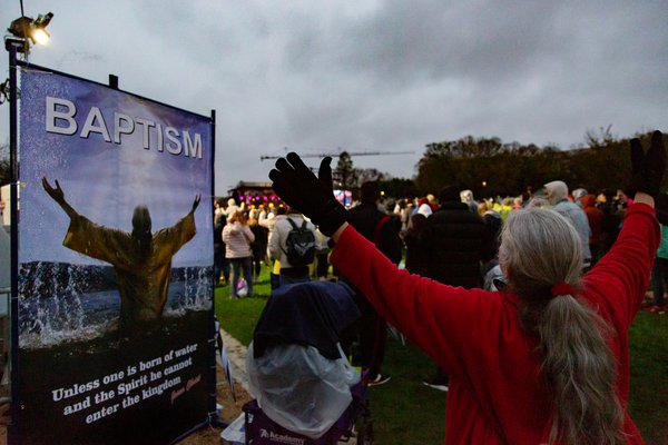 A woman opens her arms in prayer during a rally in Washington, D.C. thumbnail