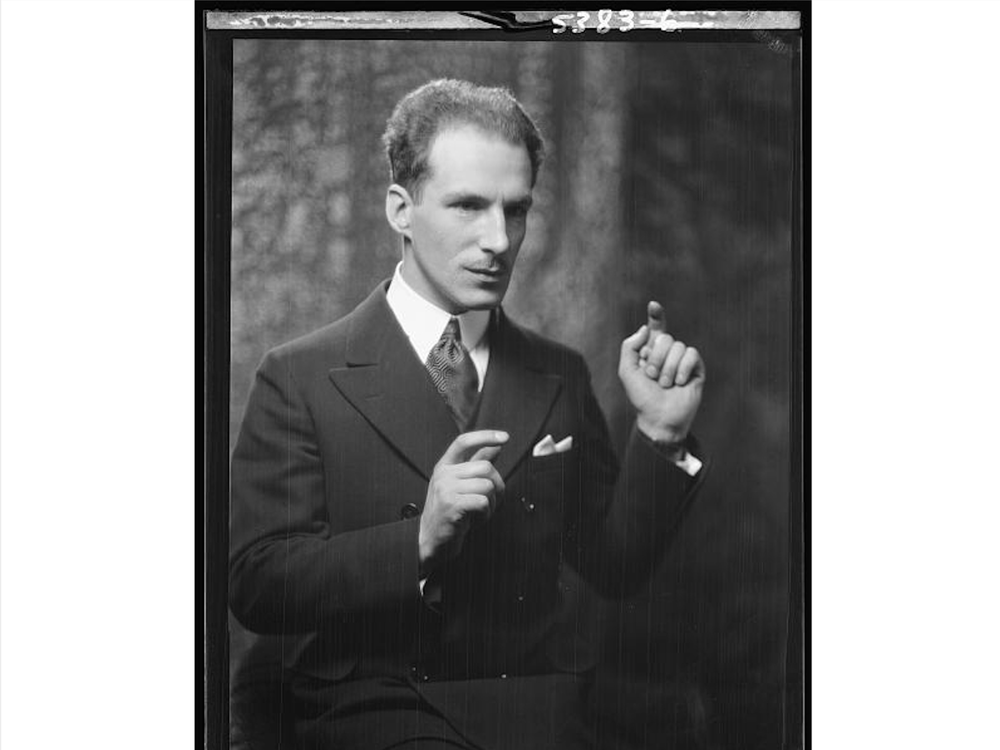 A black and white photograph of Theremin from the waist up, holding one hand up and his other to the side as though he is playing his namesake instrument