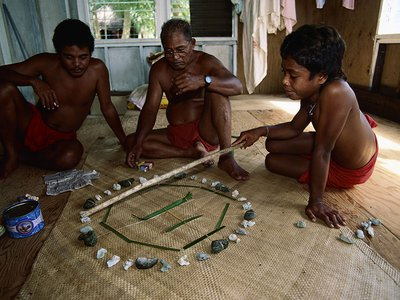Master navigator Mau Piailug teaches navigation to his son and grandson with the help of a star compass.