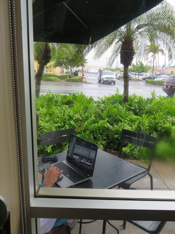 A customer enjoys coffee while browsing on a rainy morning beside Kahului, Maui's main street. thumbnail