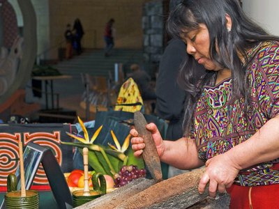 Juanita Velasco (Ixil Maya) grinds cacao beans into chocolate during the 2011 Power of Chocolate Festival. The Maya and Aztec peoples valued cacao pods as symbols of life, fertility and even currency.