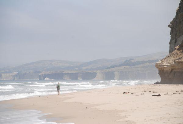 Lone fisherman on a misty California beach thumbnail
