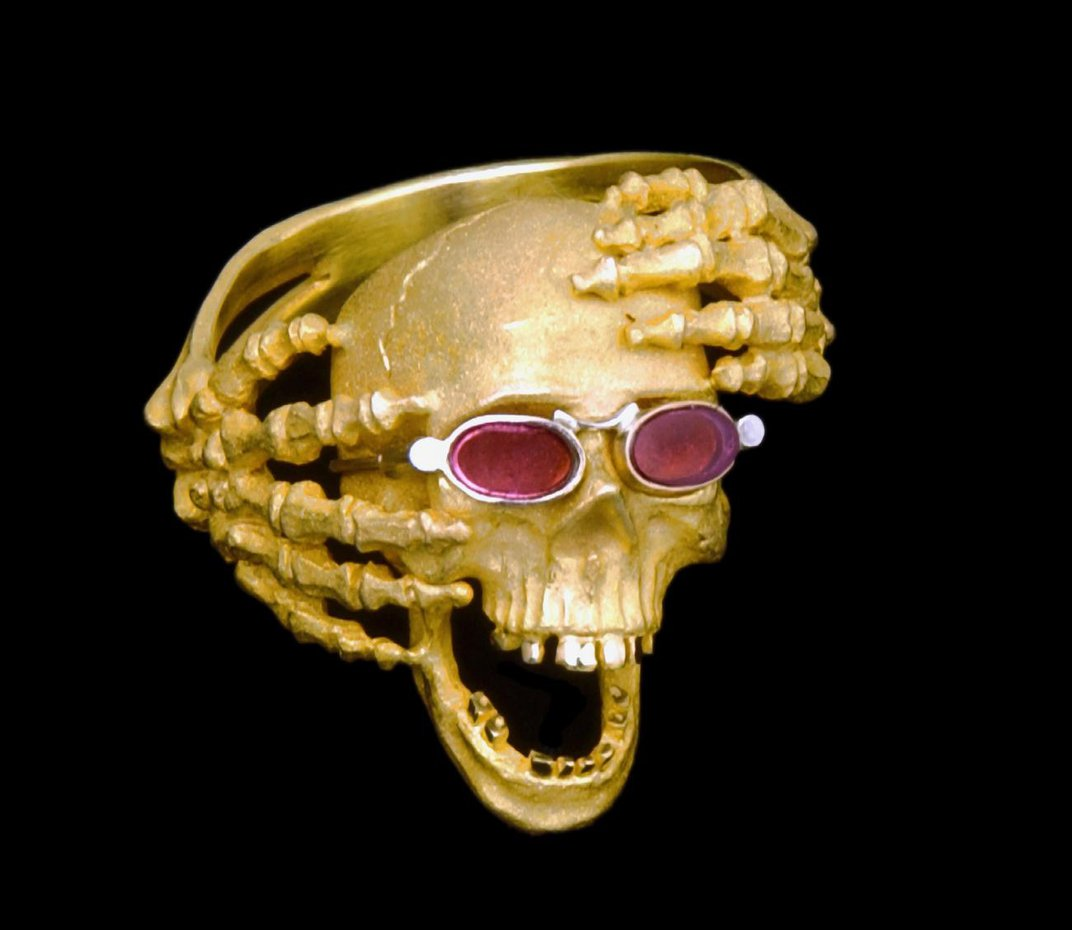 A photograph of a skull with sunglasses and skeleton hands holding it.