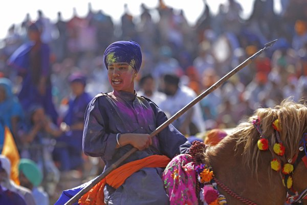 A young boy performing stunts while riding a horse during hola mohalla fair. thumbnail