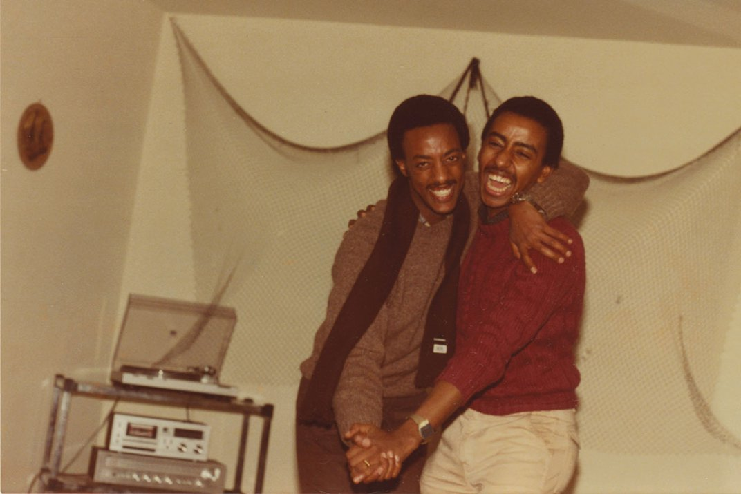 Two men embrace, as if dancing, while smiling and laughing, in what appears to be a basement room.