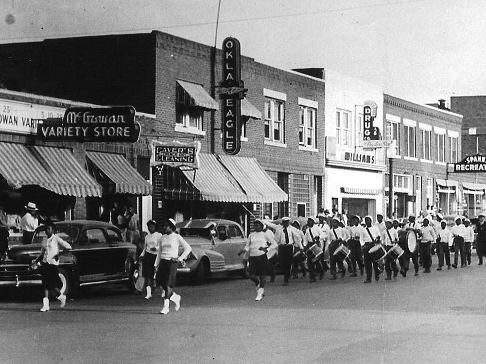 View of an unspecified parade on Greenwood Avenue, Tulsa, Oklahoma, 1930s or 1940s. Among the visible businesses are the offices of the Oklahoma Eagle newspaper at 117 North Greenwood Avenue