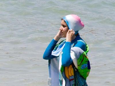 A woman wearing a burkini at the beach