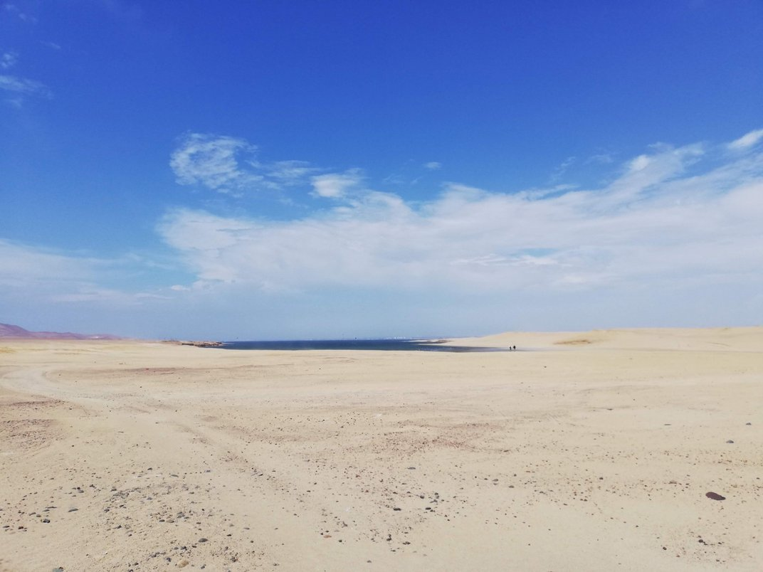 A body of water, called Cequion Bay, can be seen in the distance. The bay is surrounded by a flat, sandy, desert landscape.