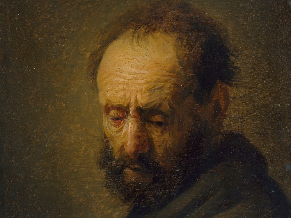 A yellow-toned, dark portrait of a white man from the chest up; his forehead wrinkles are prominent; he turns toward the viewer and wears a dark cloak, with balding, scraggly brown hair and beard, looks despondently downward