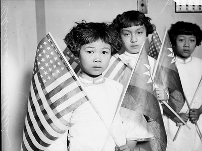 Group portrait of three Chinese children, each holding an American flag and a Chinese flag, in a room in Chicago, 1929