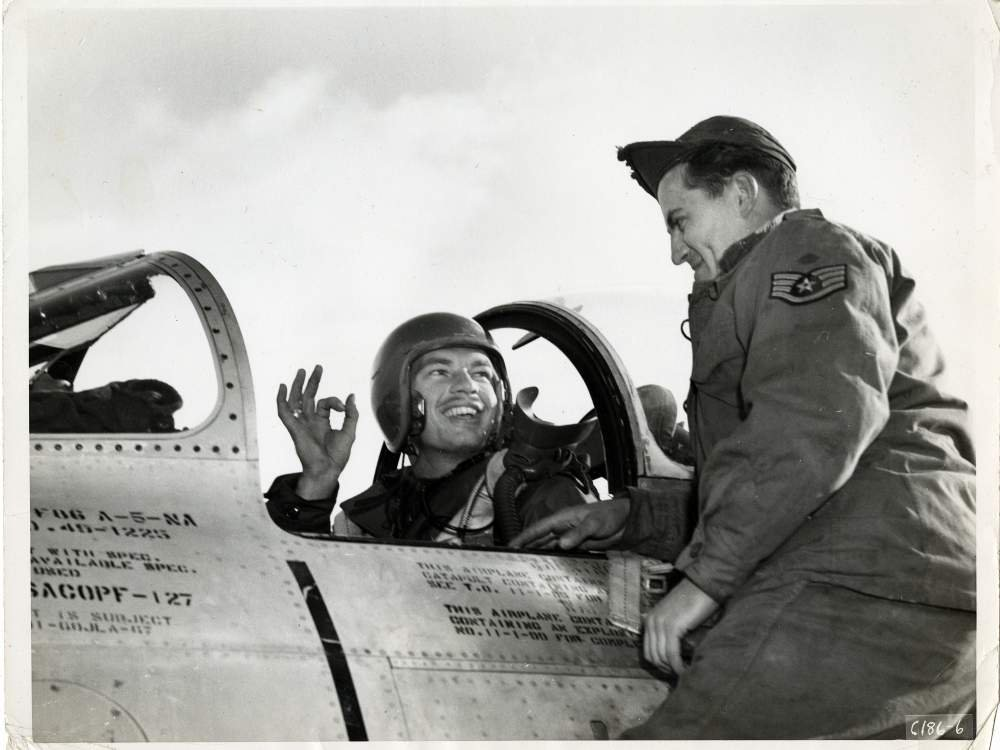 Lt. Ward Hitt, Jr., sitting in the cockpit of his North American F-86A Sabre fighter, gives his crew chief the OK hand sign, South Korea.