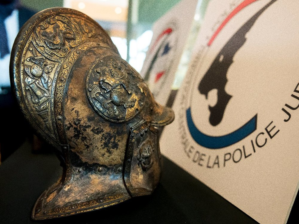 A close up look at an intricately carved helmet, with motifs of flowers, swords, torches and warriors on it