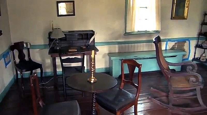 The main room on the lower floor of Poe's cottage. The mirror and the rocking chair belonged to the author. (image: Bronx Historical Society)