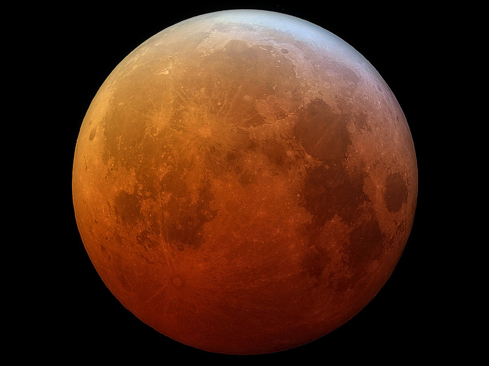 A photo of a lunar eclipse where the moon looks red-orange at the bottom which fades up to normal gray-white at the top