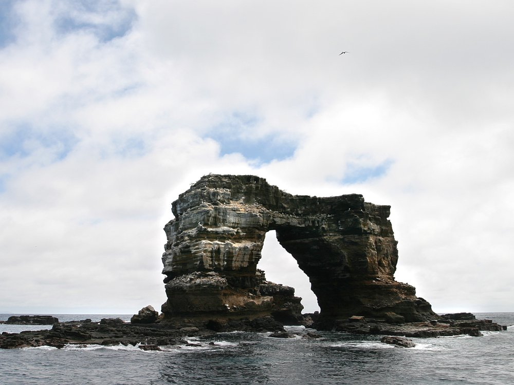 A photograph of Darwin's Arch in the Galàpagos Islands. The rock formation is two pillars attatched by a natural rock bridge. It stands itself in the ocean with a cloudy sky in the background.