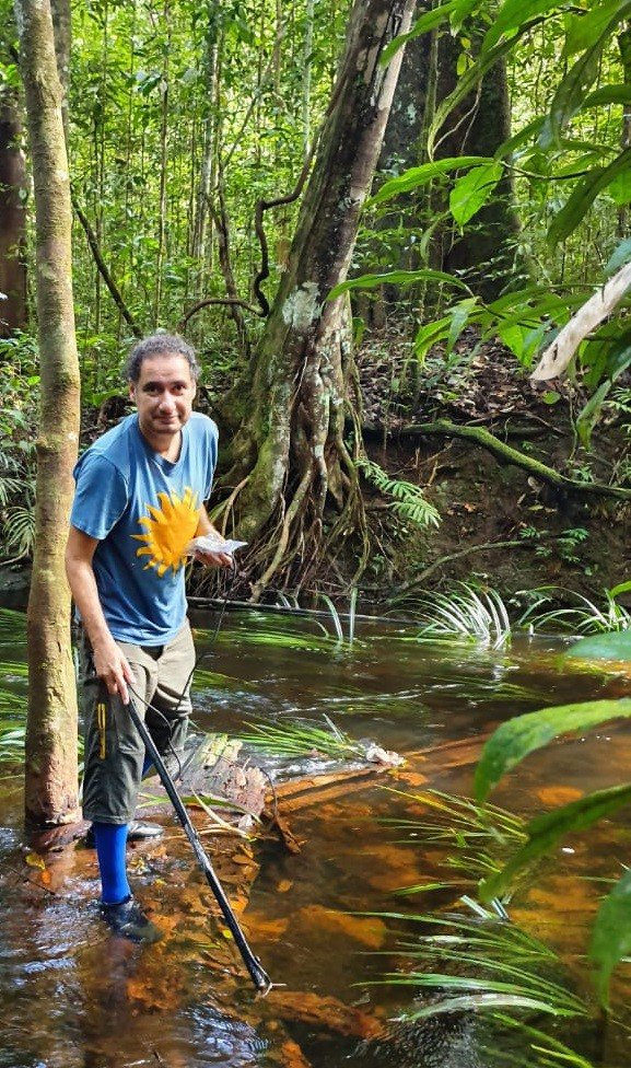 A man stands with a stick in shallow water.