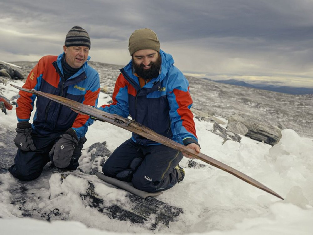 Archaeologists examine the second ski after it was freed from the ice