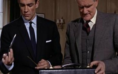 Desmond Llewelyn as Q in License to Kill showing Bond (Timothy Dalton) the camera gun that, when put together, became a sniper rifle.