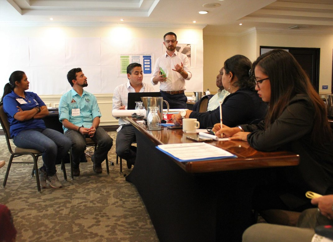 A group of people sitting at a table in a conference room.