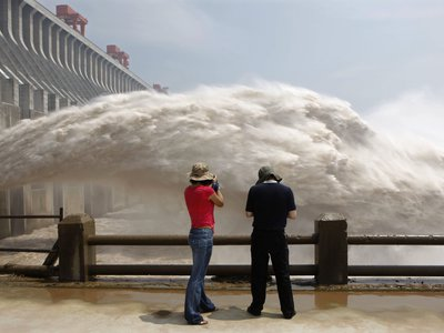 People take pictures of water gushing from the reservoir of China's Three Gorges Dam, the largest hydropower station in the world.
