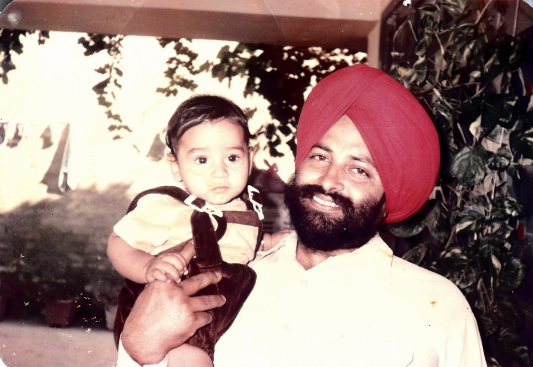 A snapshot of a man in a turban holding a toddler in overalls.