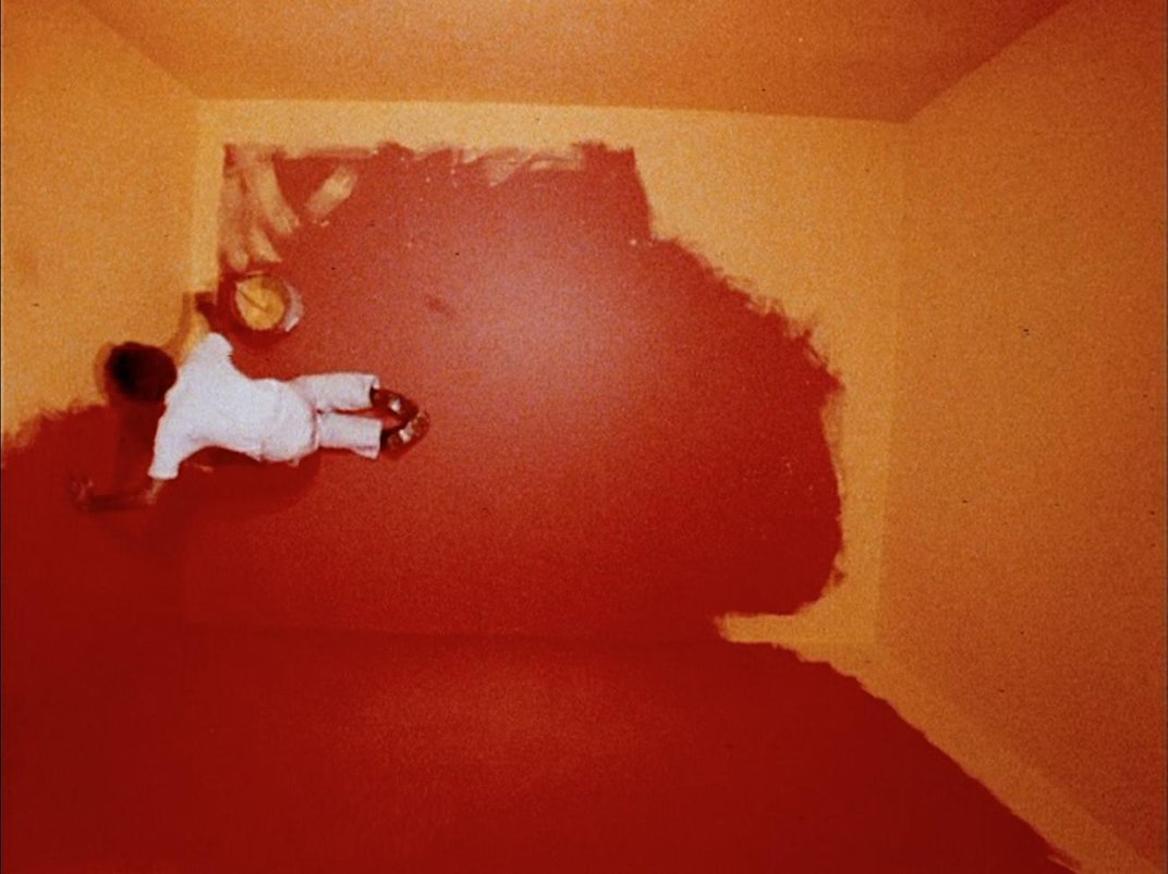 A photograph from above of a man painting a room.