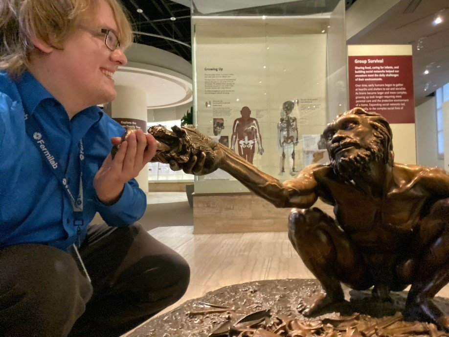 """A visitor squats to take a bronze fish being offered by a life-size bronze statue of Homo heidelberensis on display in the """"Hall of Human Origins"""" at the Smithsonian's National Museum of Natural History."""