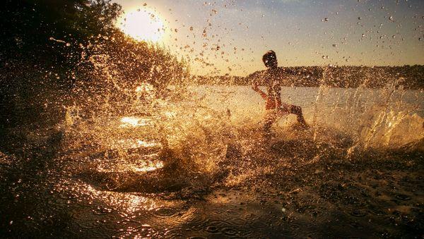 Boy running into a lake at sunset thumbnail