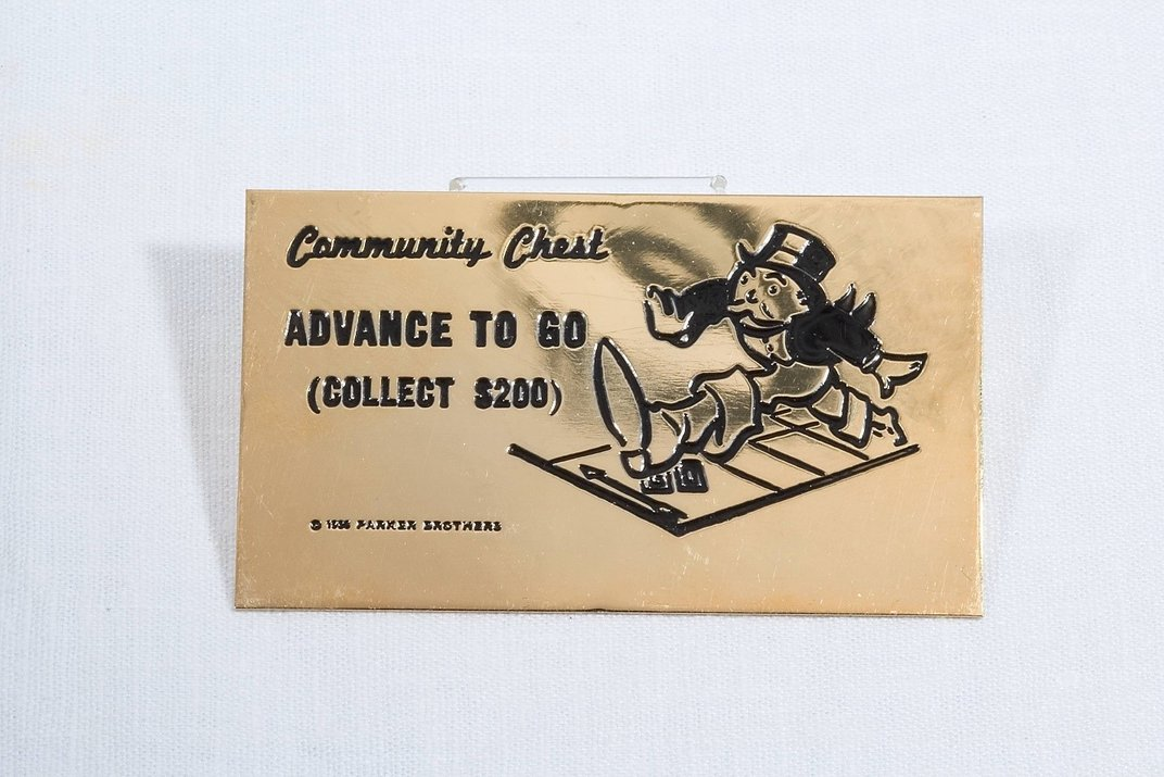 """23-carat gold-plated Community Chest card with """"Advance to Go (Collect $200)"""" engraved in black."""