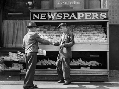 The newspapers on sale at this New York City newspaper stand likely contained some of the same comics and articles, thanks to the advent of syndication in the early 20th century.