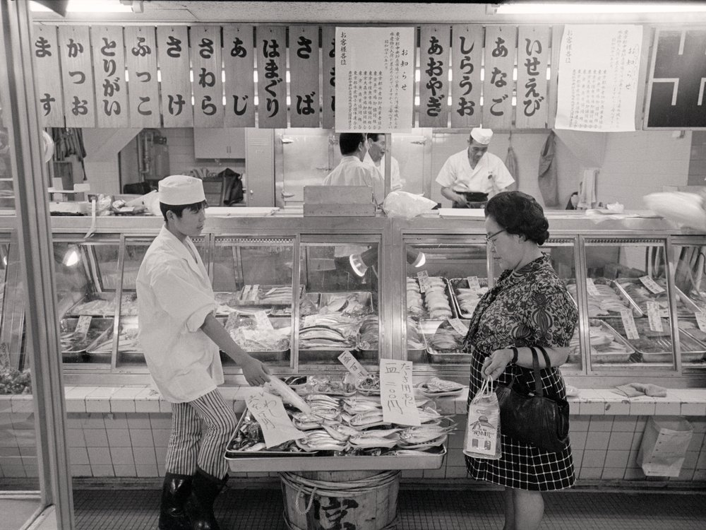 A woman seems hesitant about buying fish at a shop in Tokyo in 1973