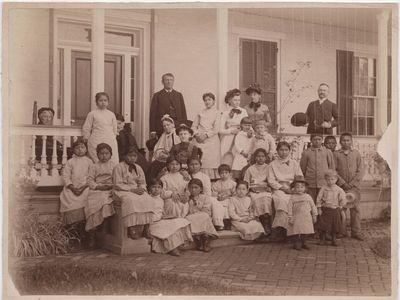 Richard Henry Pratt, founder of the Carlisle Indian Industrial School, poses alongside students around 1900.
