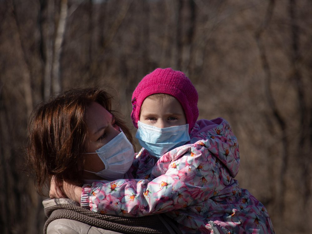 A photo of a woman holding a small child in her arms. Both are wearing masks.