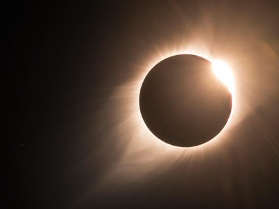 """As the 2017 North American total solar eclipse comes to an end, the famous """"diamond ring"""" becomes visible. The sun's corona is also visible, with the star Regulus to the left."""