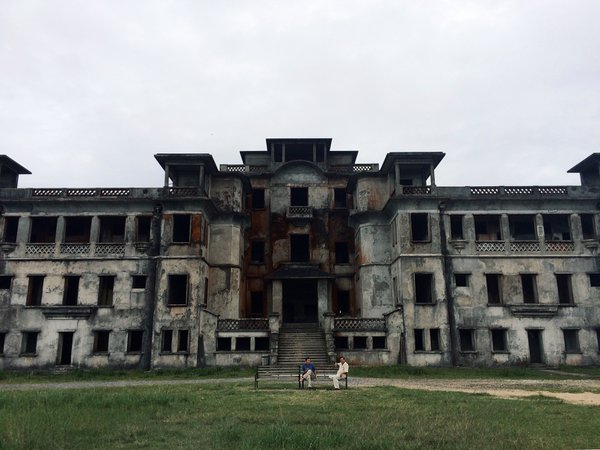 Two men sit outside an abandoned casino in Cambodia thumbnail