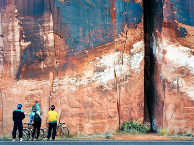 """Cyclists Inspecting Ancient Petroglyphs, Utah, 1998: Texas-based photographer Terry Falke captures several of the exhibition's themes in this image of cyclists examining petroglyphs and bullet holes in a stratified rock face by the side of the road in Utah. """"You've got the ultimate strata, which is man-made, so the idea is that we are impacting, we're leaving our mark on the Earth over time as well,"""" says Talasek."""