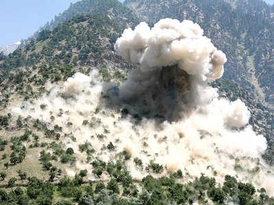 A bomb blast engulfs a mountainside near the town of Barg-e Matal in Afghanistan.