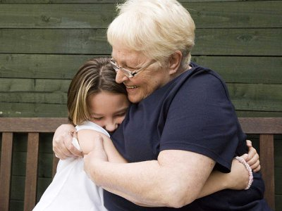 A woman hugs her granddaughter. Some scientists believe child care from grandmothers influenced human evolution.