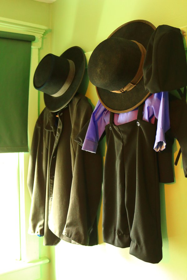 Amish clothing and hats hanging on a wall thumbnail