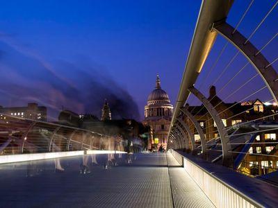 Pedestrians cross London's Millennium Bridge at dusk toward the lit dome of St. Paul's Cathedral.