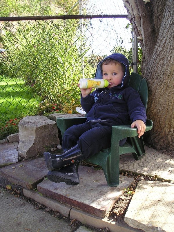 Boy lounging in a chair drinking a bottle of milk thumbnail