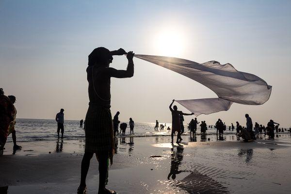 People drying cloths in sea breeze during gangasagar  thumbnail