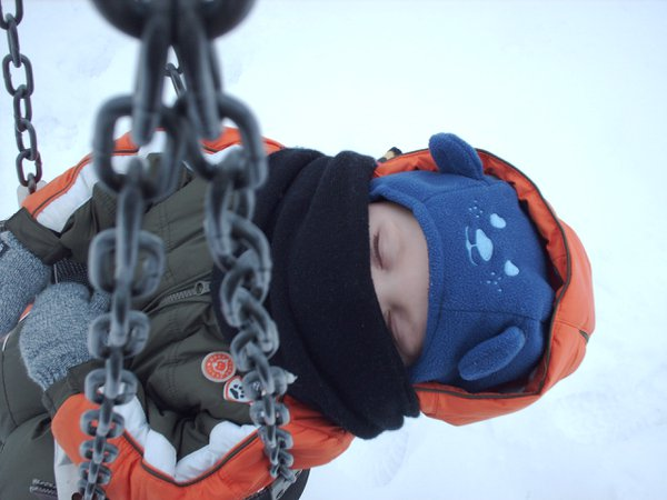 Boy sleeping in a swing in the middle of winter thumbnail