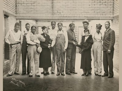 This 1936 photograph from the collections of the National Portrait Gallery—featuring eight of the nine Scottsboro Boys with NAACP representatives Juanita Jackson Mitchell, Laura Kellum, and Dr. Ernest W. Taggart—was taken inside the prison where the Scottsboro Boys were being held.