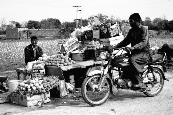 Fruit vendor and man on bike thumbnail