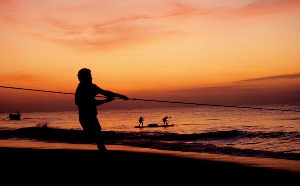 A fisherman pulling his boat on the seashore. thumbnail