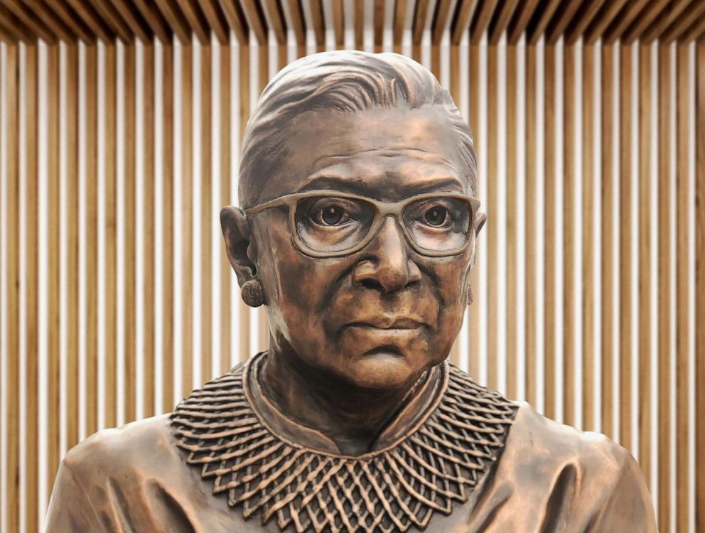 A close up of the bronze sculpture of RBG's face, with her distinctive collar and square glasses