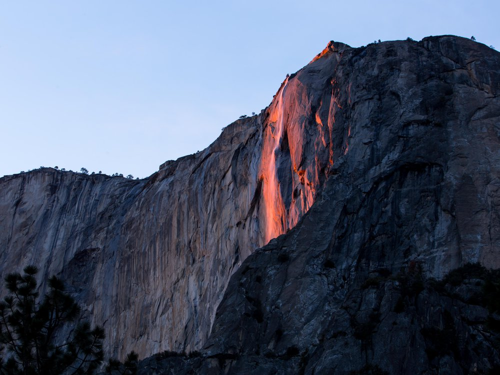 The photo shows Horsetail Falls glowing a fiery orange color.